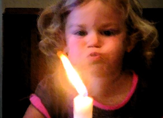 Слатко девојче се труди да дувне свеќа