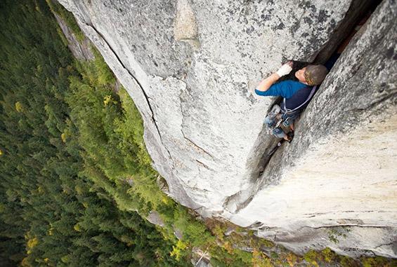 Екстремен алпинист во пукнатина на карпа. Фотографија на Пол Брајд