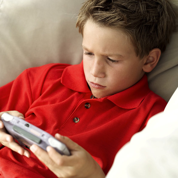 Young Boy (8-10) Sitting on a Couch Playing a Video Game