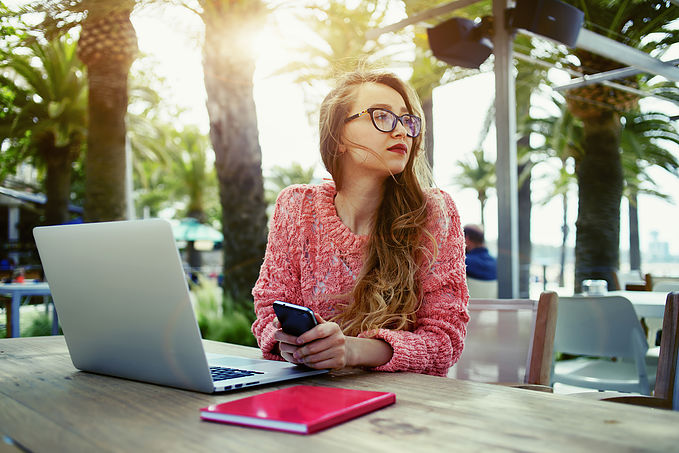 Attractive female freelancer hold smart phone while sitting at w