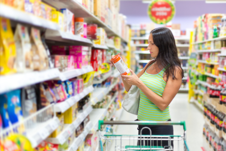 Woman checking the food labels in the supermarket