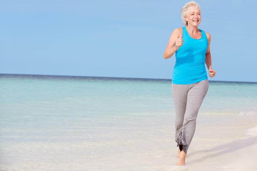 Senior Woman Running On Beautiful Beach