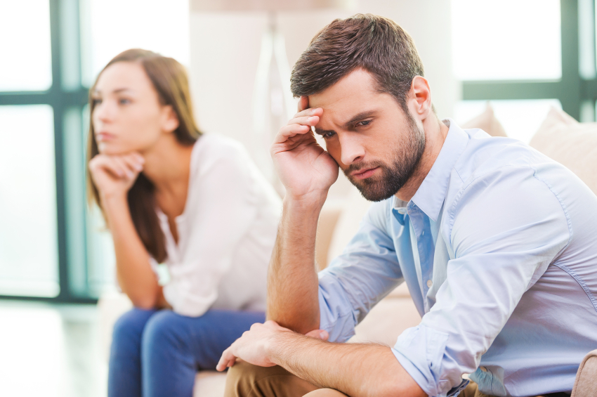 Relationship breakdown. Depressed young man holding hand on head and looking away while woman sitting behind him on the couch