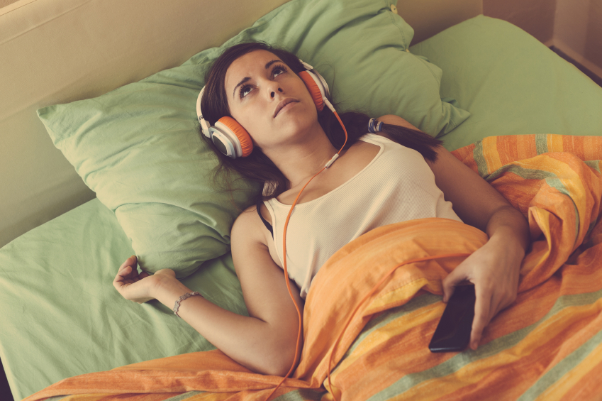 Young Woman Listening Music with Headphones on the Bed