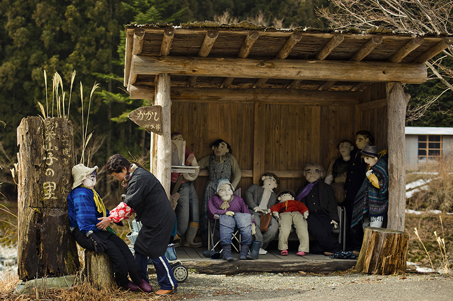 Tsukimi Ayano arranges a scarecrow at a bus stop in the mountain village of Nagoro