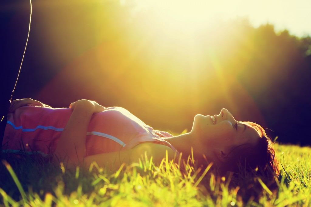 Young pretty woman lying on the grass at summer sunset. Natural