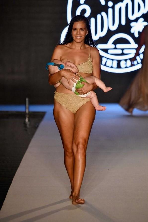 Модел прошета на модната писта доејќи го своето дете