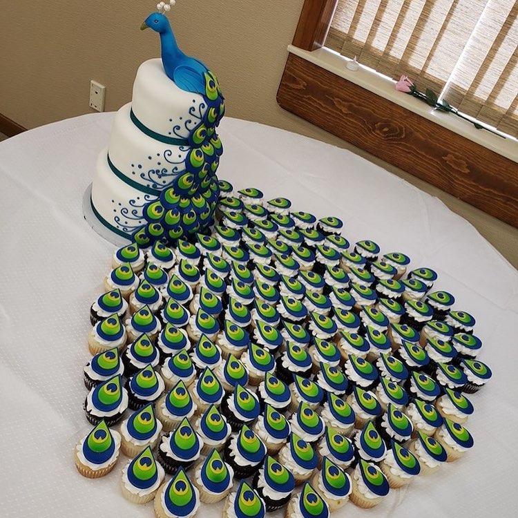 Свадбена торта во форма на паун со долг опаш од колачиња