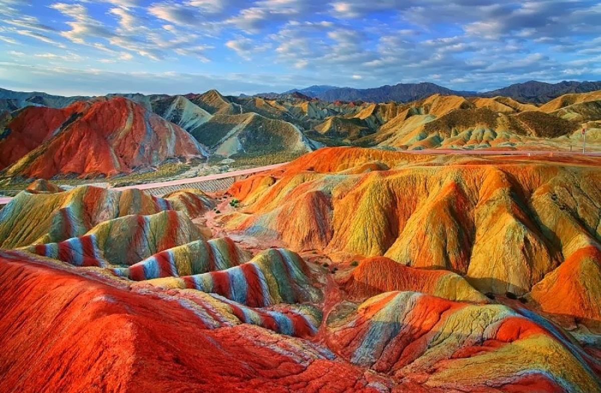 Шарени планини со боја на виножито што се слева по врвовите