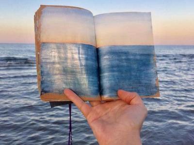 Артистка скицира морски пејзажи кои потоа ги фотографира држејќи ги над крајбрежјето